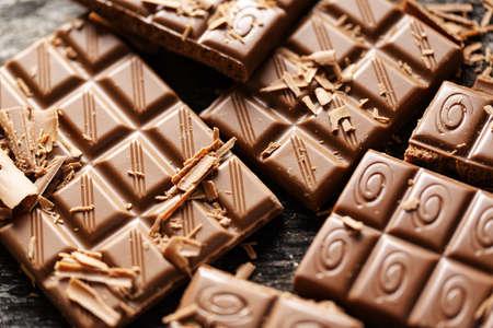 Broken chocolate bars on dark background. Closeup. Chocolate background. Closeup