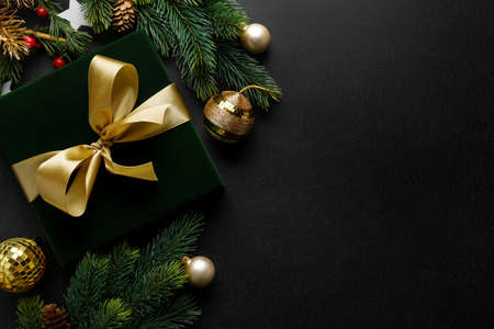 Wrapped gift with green bow and baubles on dark backgrounds. 免版税图像 - 159400468