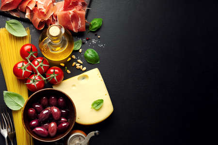 Traditional italian food background with spaghetti tomatoes cheese olives and oil on dark background. 免版税图像 - 159400475