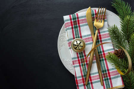 Christmas golden cutlery on plate with ribbon on dark background. 免版税图像 - 159399389
