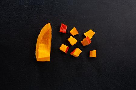 Cut pumpkin chunks on dark background. Mockup. Closeup 免版税图像
