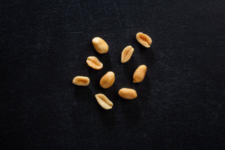 Peanut chunks in bowl on dark background. Mockup