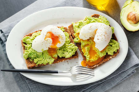 Toasts with avocado and eggs served on plate. Closeup. Banque d'images