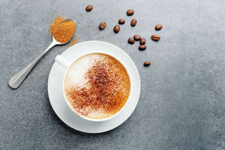 Tasty appetizing cappuccino in cup with beans on concrete background.