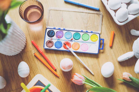Easter lifestyle background with tools for painting eggs and flowers on wooden table. View from above.