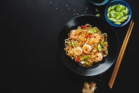 Tasty appetizing asian noodles with vegetables and shrimps on plate on dark background. 免版税图像