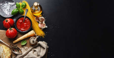 Italian food background with spaghetti vegetables and tomato sauce on dark background. Top view. banner