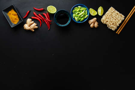 Different asian food ingredients on dark background. Top view.
