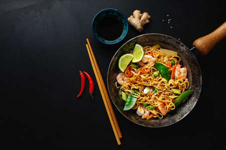 Tasty appetizing asian noodles with vegetables and shrimps on pan on dark background. 免版税图像