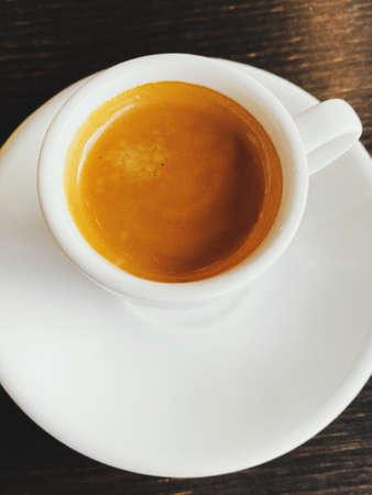 Tasty fresh italian espresso in white ceramic cup on table in cafe. Closeup