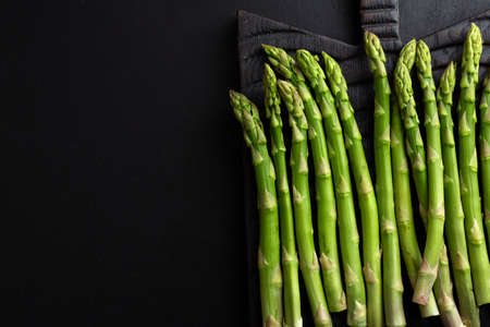 Green asparagus on dark background ready for cooking. View from above. 免版税图像
