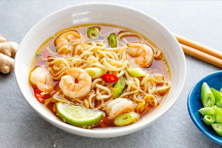 Tasty appetizing asian noodles with vegetables and shrimps in bowl on concrete background.
