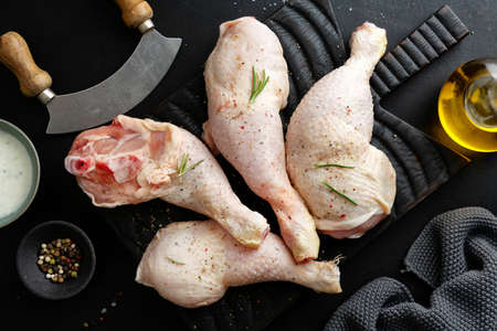Raw chicken legs with spices on board on dark background. Top view. 免版税图像
