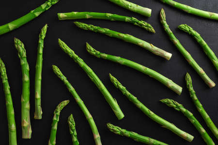 Green asparagus on dark background ready for cooking. Pattern mockup food background 免版税图像