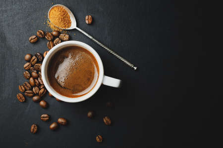 Tasty steaming espresso in cup with coffee beans. View from above. Dark background.