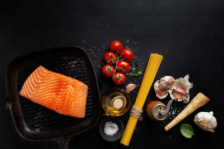 Raw salmon with spices on dark background. Top view
