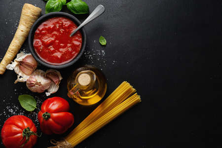 Italian food background with spaghetti vegetables and tomato sauce on dark background. Top view.