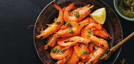 Tasty shrimps with spices and sauce on pan on dark background. Top view.