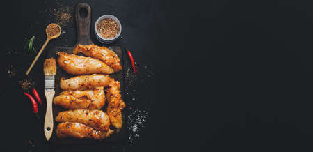 Raw marinated chicken breast on dark background with spices ready to cook. Banner.
