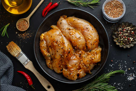 Raw marinated chicken breast on dark background with spices ready to cook.