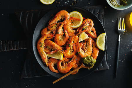 Tasty shrimps with spices and sauce on plate on dark background. Top view.