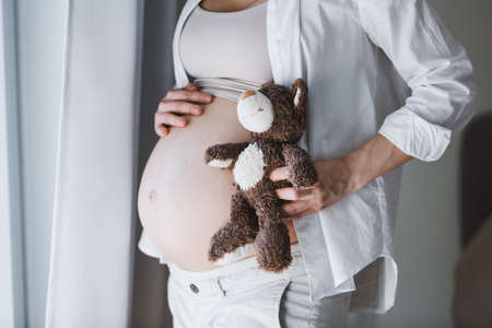 Pregnant woman with toy teddy bear listening baby. Lifestyle. Maternity concept.