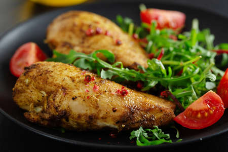 Tasty grilled chicken with vegetables and salad served on dark table.