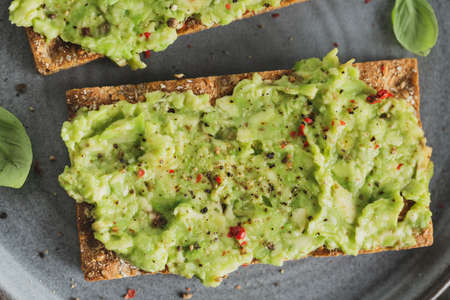 Tasty appetizing crispbread with mashed avocado served on plate. Stockfoto