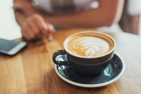 Tasty fresh cappuccino in cup on wooden table. Unrecognizable business woman on background