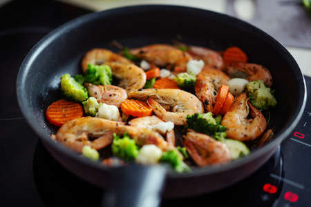 Cooking shrimps with vegetables on pan. Home cooking or healthy cooking concept