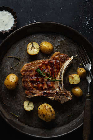 Appetizing grilled steak on old pan with potatoes on dark background. Top View. Stockfoto