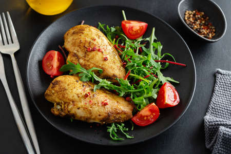 Tasty grilled chicken breast with vegetables and salad served on dark table.