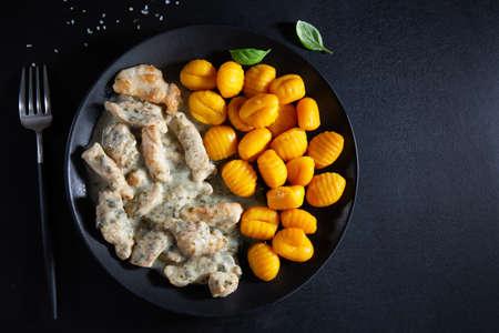 Sweet potato gnocchi with chicken in sauce served on dark plate on dark background. Stockfoto