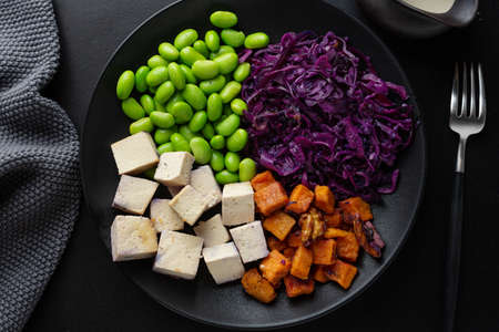 Tasty appetizing vegan bowl with tofu on plate. Top View