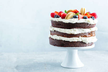 Fruity cake with fresh fruits and cream on stander on bright background.