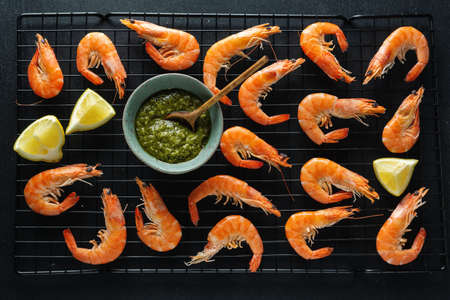 Tasty shrimps with spices and sauce on board on dark background. Top View.