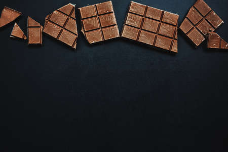 Tasty chocolate bars on dark background. View from above. Chocolate background. Stockfoto