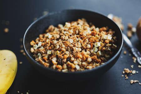Tasty homemade fruity muesli granola served in bowl on dark background. Closeup