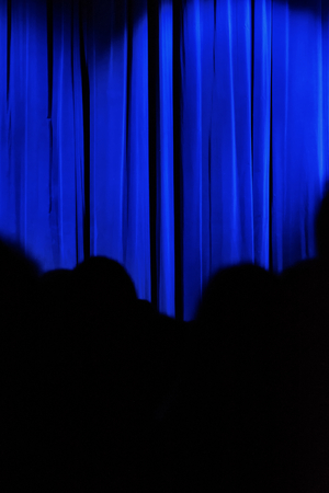 blue curtain: Blue curtain with black silhouettes of people. Stock Photo