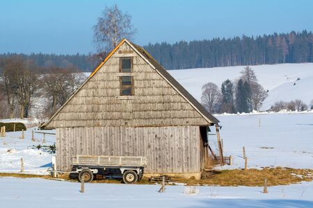 old barn in winter: Old wooden barn with a wagon in the winter landscape