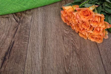 rosas naranjas: Rosas de color naranja sobre un fondo de madera marr�n