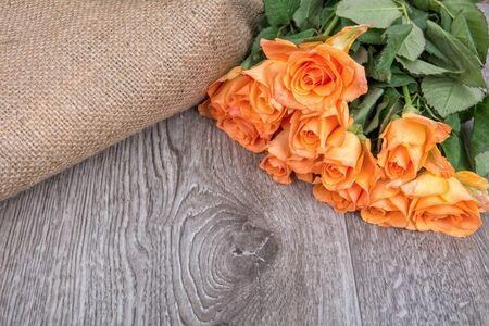 rosas naranjas: Rosas de color naranja sobre un fondo de madera gris
