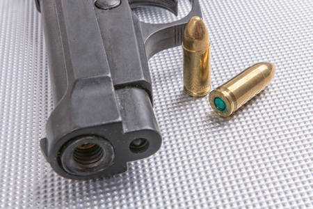 aluminium background: Gold bullets and gun on aluminium background