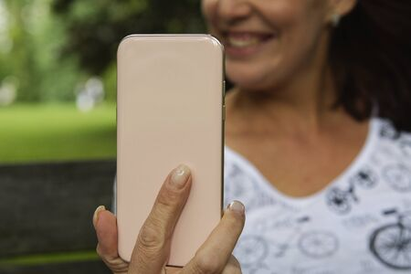 Pink mobile phone in womens hand and blurred background