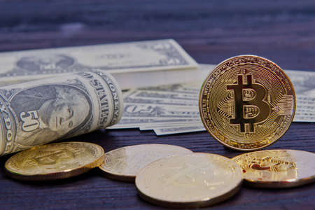 Bitcoins and dollar banknotes on a wooden table