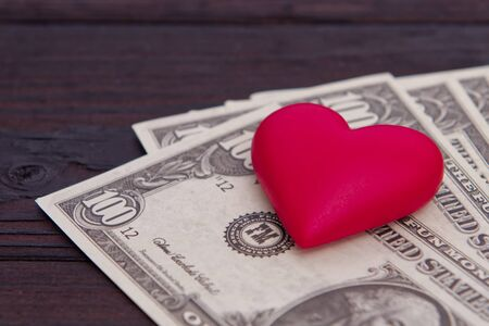Dollar banknotes and red heart on a wooden table