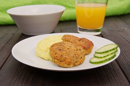Leguminous burgers and millet mash on a table