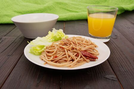 Spaghetti with nuts and dried tomatoes on a table Stock Photo