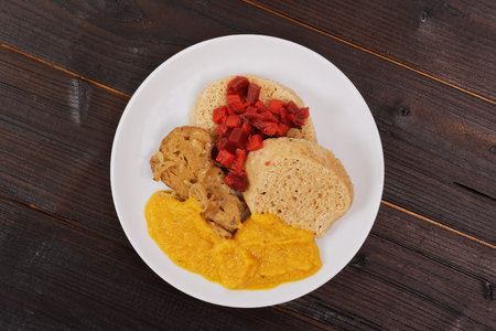 Sauce with seitan and dumplings on a wooden table