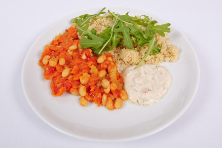 Baked beans and carrot with couscous on a white background